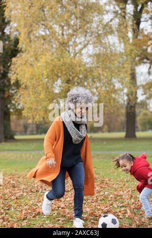 Verspielte Großmutter spielt im Herbstpark Fußball mit Enkelin - Stockfoto