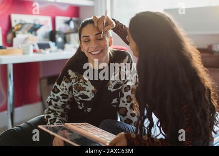 Teenager-Mädchen-Freunde, die im Schlafzimmer Make-up anwenden - Stockfoto