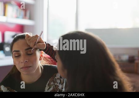 Mädchen im Teenager-Alter, die Augenschminke auf Friends Eye auftragen - Stockfoto