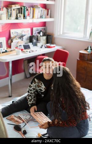 Mädchen im Teenager-Alter, die Augenschminke auf Freunde anwenden, blicken auf das Bett - Stockfoto