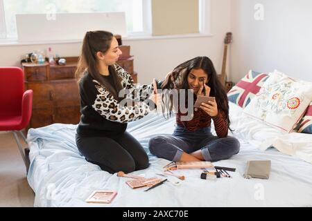 Teenager-Mädchen tragen Make-up auf und putzen Haare auf dem Bett - Stockfoto
