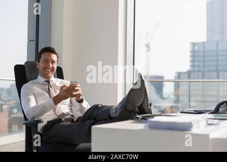 Hochformat selbstbewusster Geschäftsmann mit Smartphone mit Füßen auf dem Schreibtisch im Hochhaus - Stockfoto