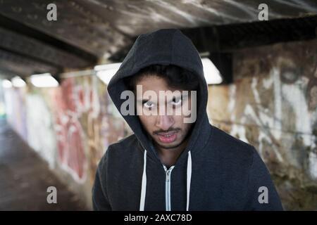 Porträt bedrohlicher junger Mann im städtischen Tunnel - Stockfoto