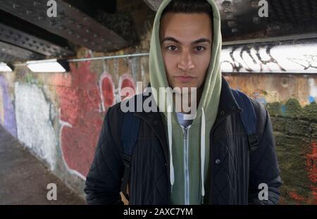Portrait seriöser, zäher junger Mann, der im städtischen Tunnel hoody trägt - Stockfoto
