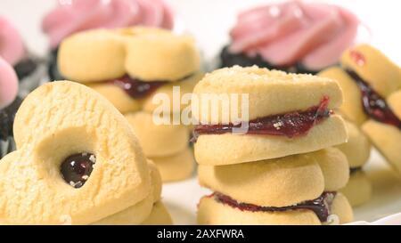Schokoladenkuchen mit Himbeer-Buttercreme-Aufschäumen und herzförmigen Plätzchen schließen sich auf weißem Hintergrund, Draufsicht. - Stockfoto