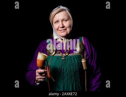 Studio-Porträt einer reifen blonden Frau in einem Wikinger-Kostüm, mit einem Kolben und einem Horn zum Trinken. Porträt eines Liebhabers lebendiger Geschichte - Stockfoto