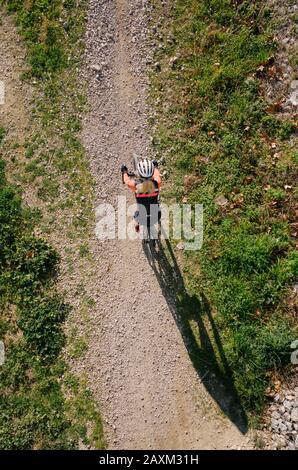 Radfahrerin, die mit dem Kies Adventure Bike auf einer Strecke von oben mit langem Schatten fotografieren kann - Stockfoto