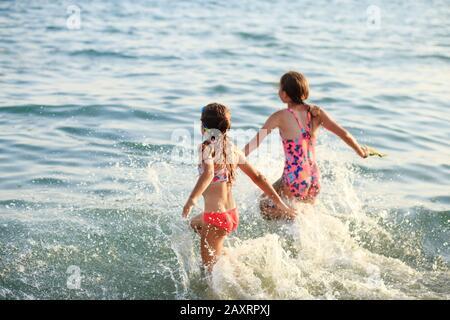 Zwei Niedliche Kleine Mädchen, die bei Sonnenuntergang mit Wellen am Meer spielen. Sommer Sunny Day, Ocean Coast, Happy Kids Konzept, weich fokussiert - Stockfoto