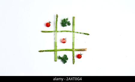 Tic Tac Toe mit Essen, Spargel Grünkohl, Tomaten, Konzept abnehmen, Entscheidung, Wahl Sieg - Stockfoto
