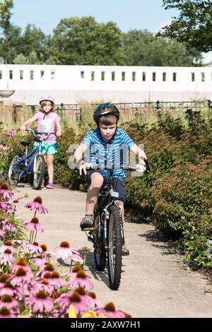 Ein elfjähriger Junge fährt mit dem Fahrrad im Beuter Riverwalk Park in Mishawaka, Indiana, USA, während seine neunjährige Schwester im Hintergrund beobachtet. - Stockfoto