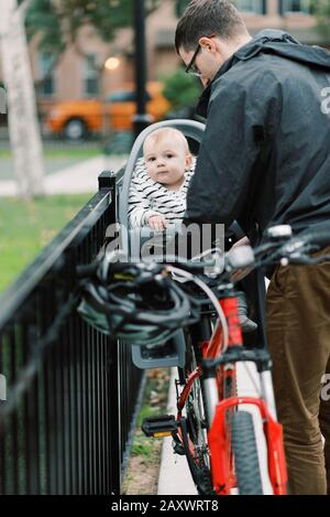 Ein junger Vater, der seinen Sohn auf seinem Fahrradsitz umreibt. - Stockfoto