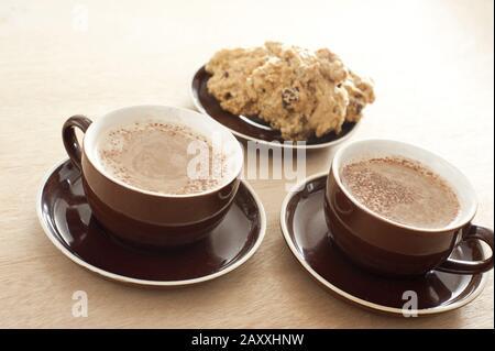 Zwei braune Keramikbecher und Untertasse mit frisch mattem Kaffee, serviert mit einem kleinen Teller mit geschnittenem Kuchen auf einem beigefarbenen Hintergrund - Stockfoto