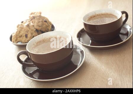 Kaffeezeit mit zwei generischen braunen Tassen und Untertöpfen von mattem, frischem Kaffee, serviert mit einem Teller geschnittenem Kuchen, konzentrieren Sie sich auf die Tasse im Vordergrund - Stockfoto