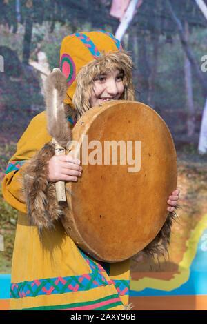 Weibliches Kind tanzt mit Tambourin in nationaler Kleidung indigene Bewohner Kamtschatka. Feier Koryak Nationalfeiertag Hololo Tag des Siegels - Stockfoto