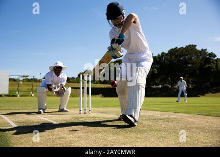 Cricket-Spieler schießen im Ball