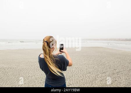 Teenager-Mädchen, die Bilder mit einem Smartphone am Strand, St. Simon's Island, Georgia, sprechen - Stockfoto