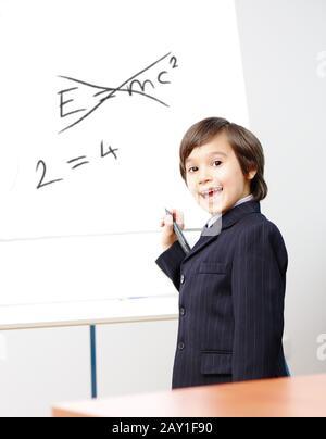 Der kleine Genius-Junge schreibt E=mc2 auf das Board - Stockfoto