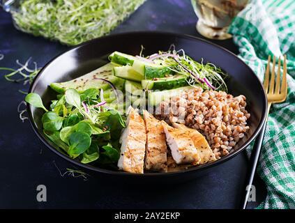 Mittagssalat. Buddhaschüssel mit Buchweizenporridge, gegrilltem Hühnerfilet, Maissalat, Mikrogrüns und Daikon. Gesunde Ernährung.
