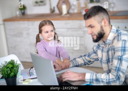 Junger Vater, der zu Hause mit Laptop arbeitet, neben der Tochter. - Stockfoto