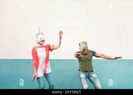 Fröhliches verrücktes Paar tanzt, während es im Freien T-rex und Einhorn-Maske trägt - Senioren haben Spaß beim Feiern des Karnevalfestes