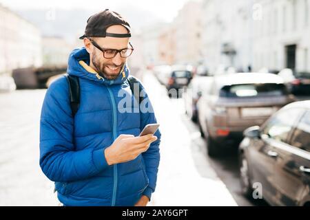 Junger bärtiger Flusspferd in blauem Anorak und Kappe, der den Anruf auf dem Smartphone entgegennimmt, mit glücklichem Ausdruck isoliert über dem Hintergrund der Großstadt. Stilvoll - Stockfoto