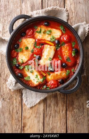 Das Mittelmeer gebackene Halloumi mit Tomaten, Paprika, Oliven in würziger Sauce in einer Pfanne auf dem Tisch. Vertikale Draufsicht von oben