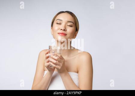 Entspannt junge lächelnde Frau trinkt sauberes Wasser.