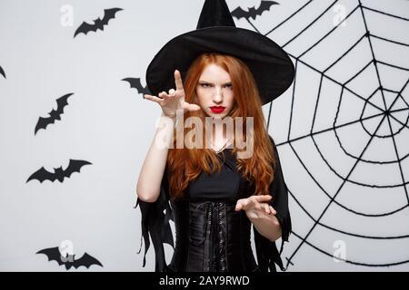 Halloween Witch Concept - Halloween Witch in Voller Länge Zaubersprüche mit ernsthaftem Ausdruck über dunkelgrauem Studiohintergrund Wi - Stockfoto
