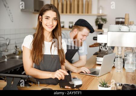 Coffee Business Concept - Schöner weiblicher Barista, der seinen Kunden mit Kreditkarte bezahlen und lächeln kann, während er in der Arbeit ist - Stockfoto