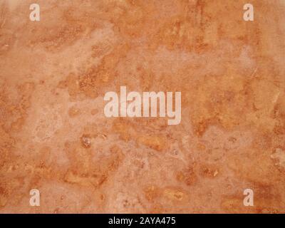 Nahaufnahme eines grob strukturierten ockerfarbenen Steingrunds