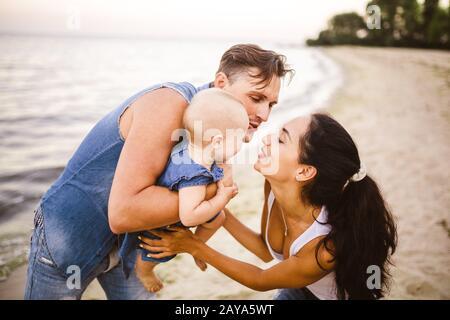 Eine junge, schöne Dreierfamilie. Mama, Papa und Tochter in den Armen meines Vaters spielen, freuen, lächeln am Sandstrand an Th