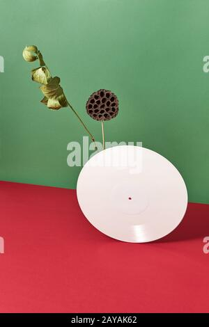 Zusammensetzung trockener Bud, Branche und weißem Vinyl audio Aufzeichnungen auf einem doppelt rot grün Hintergrund mit Platz für Text