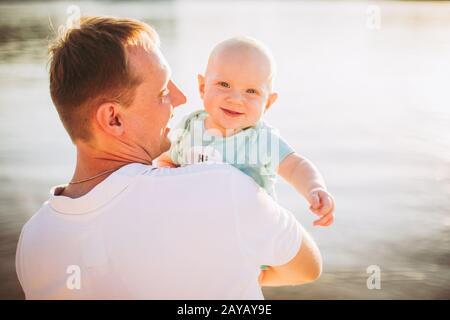 Thema Elternschaft, Sommerferien, Vater und kleiner Sohn. Der junge kaukasische Vater hält sich an den Armen, umarmt das Kind mit Blick auf die Stadt Kiew - Stockfoto