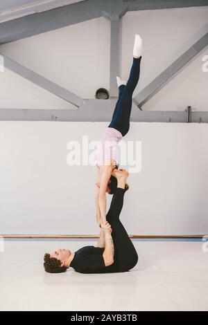 Thema ist Sport und Akreage. Ein junges kaukasisches Männer- und Frauenpaar, das akrobatisches Yoga in einer weißen Turnhalle auf Matten praktiziert. Ein Mann li - Stockfoto