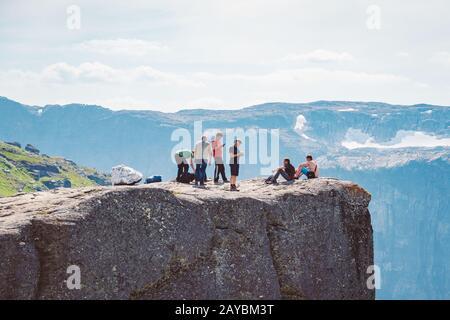 Juli 2019. Norwegen Touristenroute auf der Trolltunga. Touristen wandern in den Bergen Norwegens in sonniger Umgebung - Stockfoto