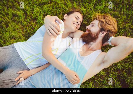 Thema ist Sport und ein gesunder Lebensstil. Auf dem grünen Gras, einem Rasen, ruht ein junges Mann- und Frauenpaar auf dem Rücken