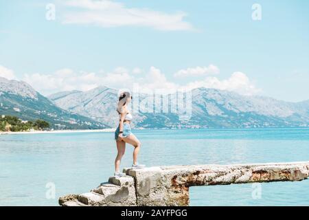 Zeit für Reisen: Schöne Frau in weißem Thema und Jeans-Shorts allein am Meer, die auf den blauen Ozean blicken und die Aussicht genießen - Stockfoto