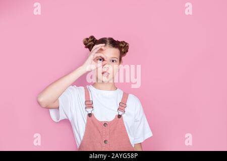 Porträt eines süßen liebenswerten Mädchens in weißem T-Shirt Mädchen, das auf pinkfarbenem Hintergrund ein Symbol macht - Stockfoto