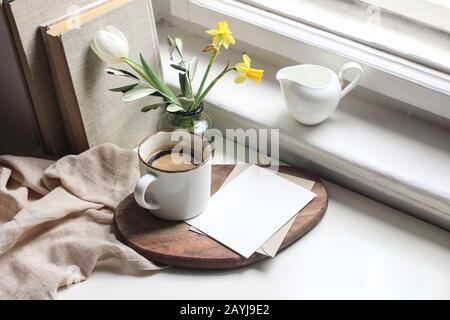 Gemütliches Stillleben im Osterfrühling. Mockup-Szene für Grußkarten. Tasse Kaffee, Bücher, Holzschneidebrett, Milchkrug und Blumenvase auf Fensterbank.