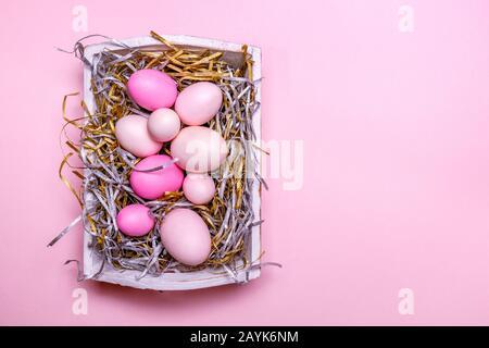 Eier in einem weißen Fach kreative Ostern Konzept. Moderne solide rosa Hintergrund. Horizontale - Stockfoto