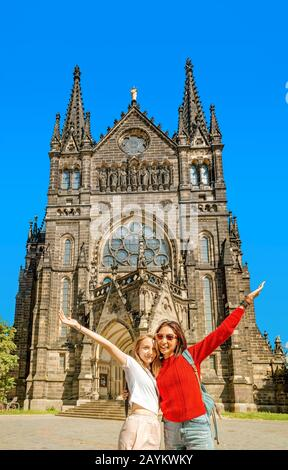 Zwei Mädchentouristen-Freunde umarmen sich vor dem Hintergrund der Peterskirche in Leipzig Stockfoto