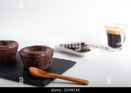 Hausgemachter Schokoladenlavakuchen auf schwarzem Teller mit Kaffee auf weißem Hintergrund - Stockfoto