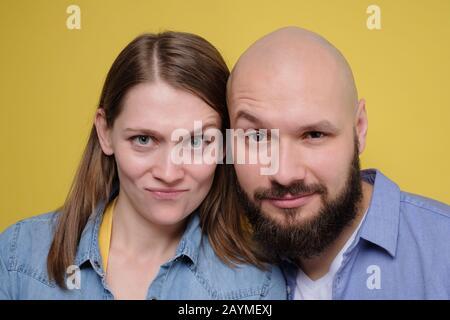 junges kaukasisches Paar, das mit Zweifeln auf die Kamera blickt, die skeptische Gesichter hat. Studio gedreht. - Stockfoto