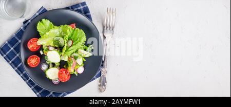 Gemüsesalat aus frischem Salat, Kirschtomaten, Gurken, Rettich, Grüns und Zwiebeln zum Mittagessen auf dem Tisch. Gesundes Speisekonzept. Space-Mockup kopieren, - Stockfoto