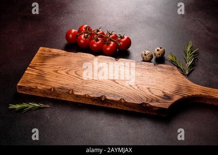 Zutaten für die Kochpaste auf dunklem Hintergrund. Kirschtomaten, Gewürze und Kräuter, die für Pasta zubereitet werden - Stockfoto