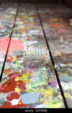 Künstlerwerkstatt oder Studiobank mit geplatzter Farbe, die in authentischer Textur auf bemalter Oberfläche aufgebaut ist
