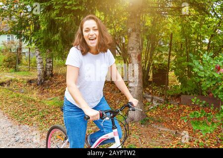 Junge Frau Reiten Fahrrad im Sommer City Park im Freien. Aktive Menschen. Hipster girl entspannen und rider Bike. Radfahren im Sommer Tag zu arbeiten. Fahrrad- und Ökologie lifestyle Konzept Stockfoto