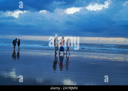 Mutter und ihre beiden Töchter gehen bei Sonnenuntergang Hand in Hand am Strand in Bali entlang - Stockfoto