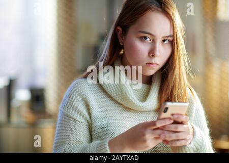 Verunglücktes modernes Teenager-Mädchen mit roten Haaren im weißen Pullover mit Smartphone, das in sozialen Medien kommuniziert und unter Cyber-Mobbing in Social Medizin leidet - Stockfoto