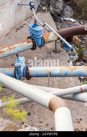 Wasserleitungen und Ventile, die Bewässerungswasser an die Farmen und Fincas im Süden von Teneras, Kanarische Inseln, Spanien liefern - Stockfoto
